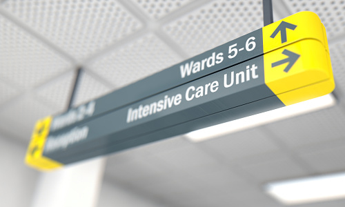 A ceiling mounted hospital directional sign highlighting the way towards the intensive care unit